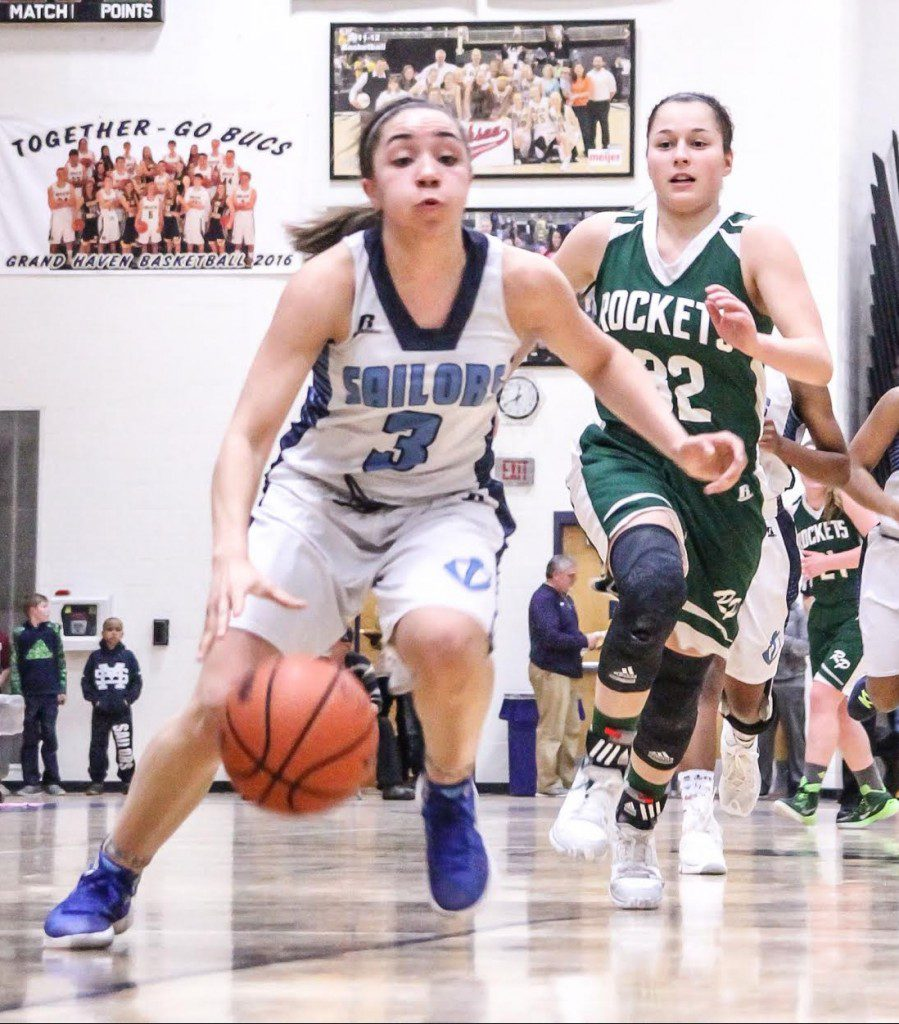 Mona Shores guard Alyza Winston drives past RP guard Elysia Mattos. Photo/Joe Lane