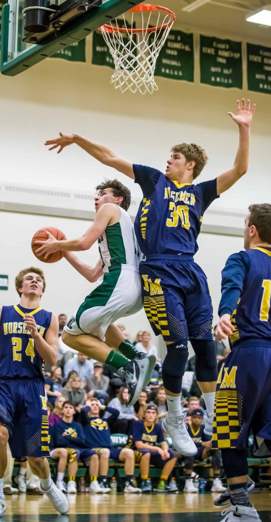 North Muskegon senior Riley Fairfield goes for the block against Western Michigan Christian guard Nate Dugener earlier this season. Photo/Tim Reilly