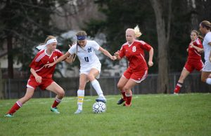 Mona Shores' Sarah Mikesell tries control the possession while No. 8 Coco McKeogh and No. 13 Sara Gray defend for Spring Lake. Photo/Marc Hoeksema