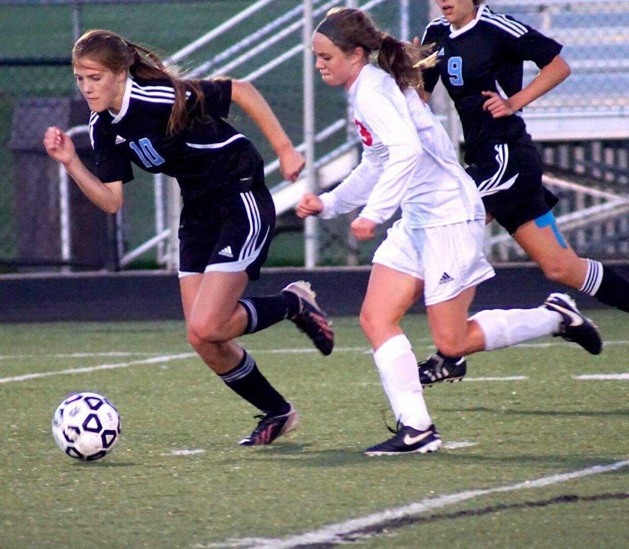 No. 3 Emily Batts runs up field against the Eagles' Maria Bolt. Photo/Leo Valdez