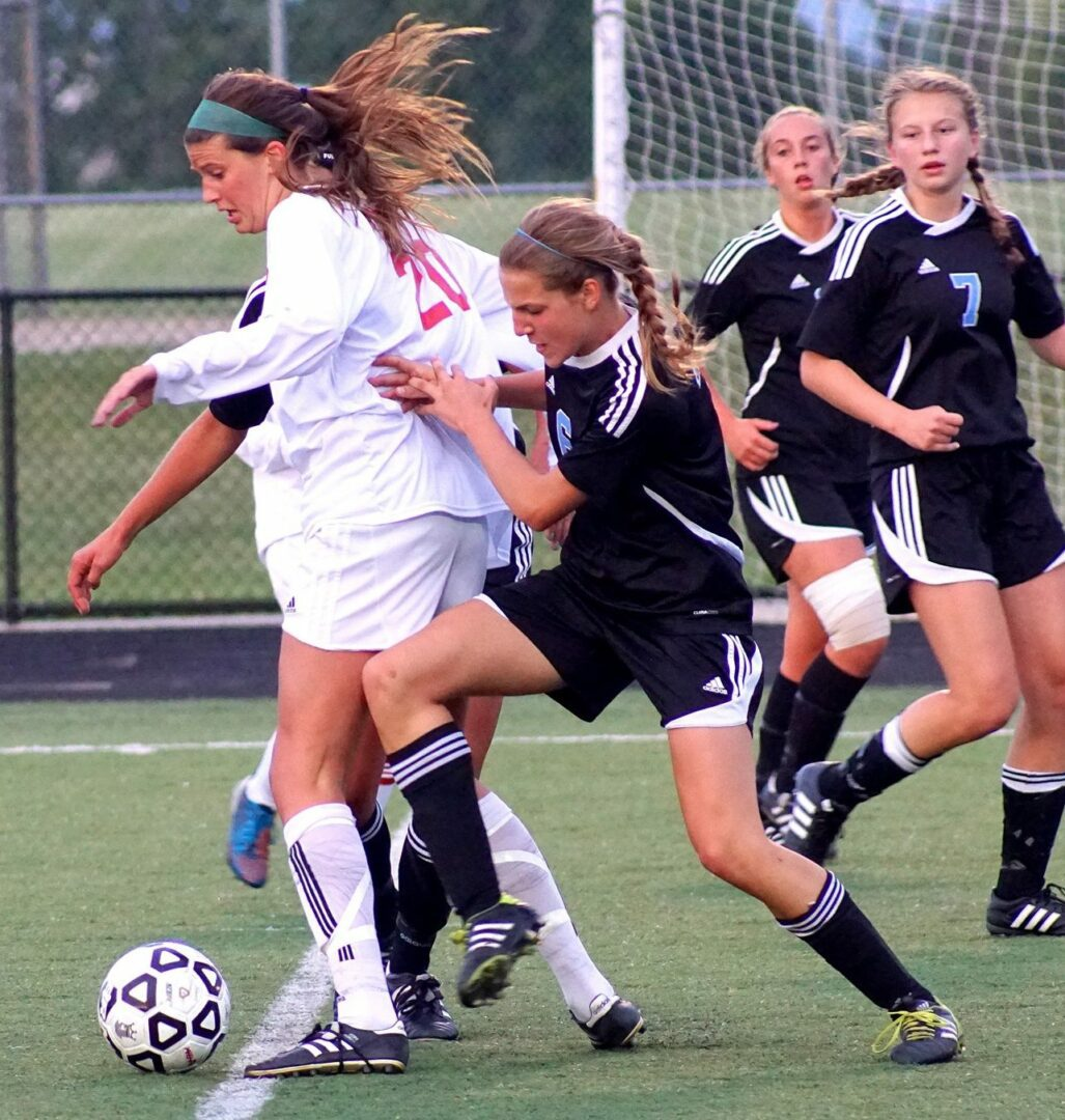 Spring Lake sophomore Coco McKeough gets pushed from behind by Sarah VanDyke. Photo/Leo Valdez
