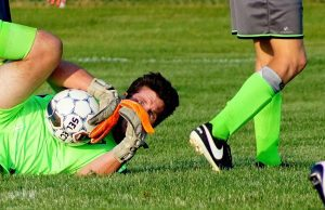 Risers goaltender Tyler Lane peeks out after making a diving save in a game on June 18. Photo/Leo Valdez