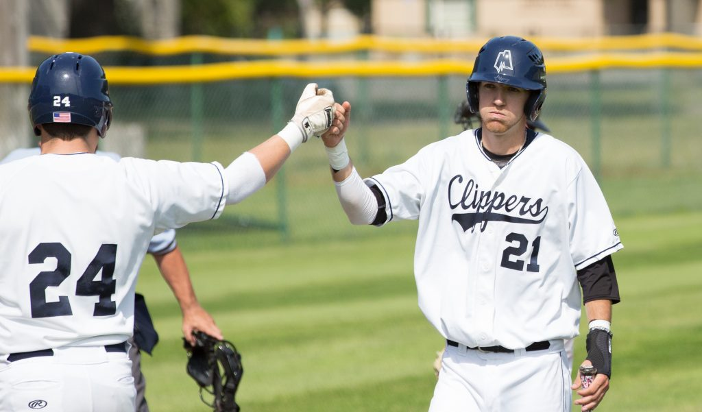 No. 21 Logan Fleener fist bumps Andrew Null after Fleener scores a run. Photo/Kevin Sielaff