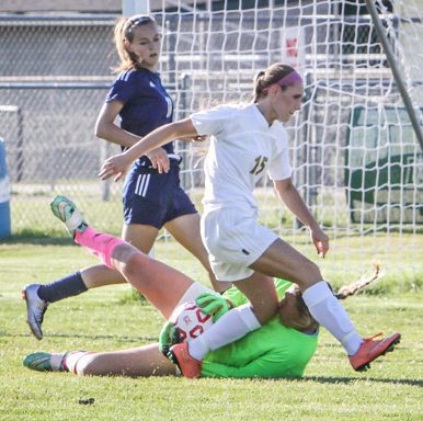 Gus Keur puts herself on the line to make the save as MCC's No. 15 Maddie Olsen nearly gets the loose ball. Photo/Joe Lane