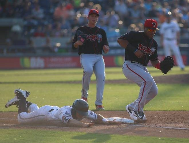 Cam Gibson slides headfirst into first base. Photo/Tom Reynolds