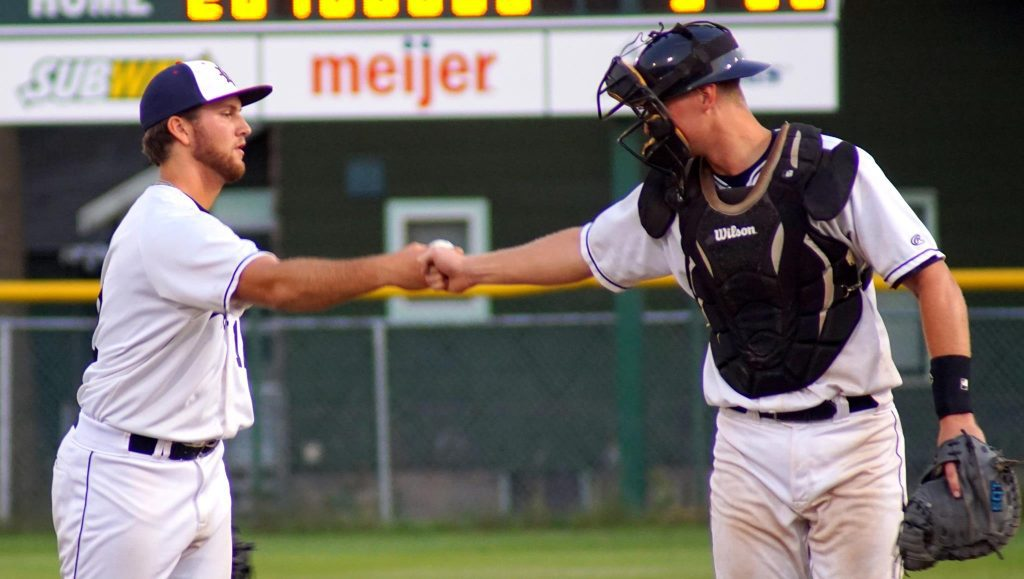 Muskegons Kyle Lawson fist bumps catcher Connor Glick after securing the win. Photo/Leo Valdez