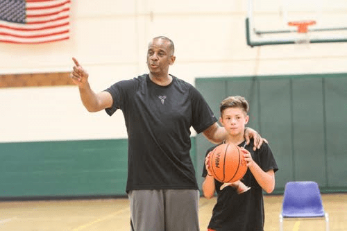 JT Johnson listens to direction from Portland Trailblazers coach Osbourne during Saturday's clinic. Photo/Joe Lane