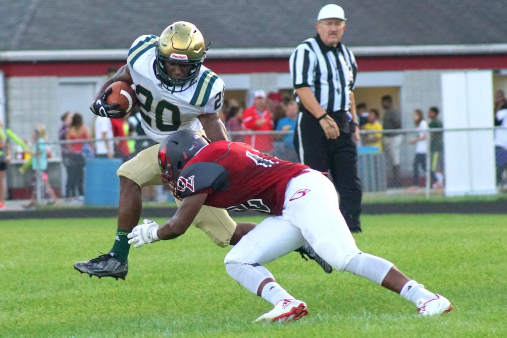 LaTommy Scott breaks a tackle for Muskegon Catholic. Photo/Leo Valdez