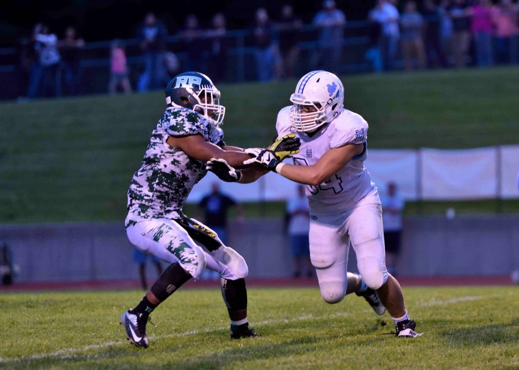 Reeths Puffer's Theo Stevenson takes on the pass rush of Mona Shores' Evan DeYoung (64). Photo/Eric Sturr