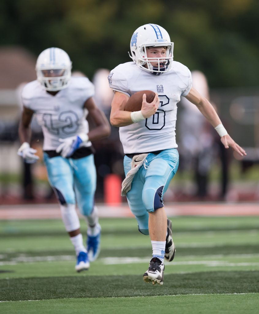 QB Tristan Robbins (6) fakes a hand-off and moves the ball up field. Photo/Kevin Sielaff