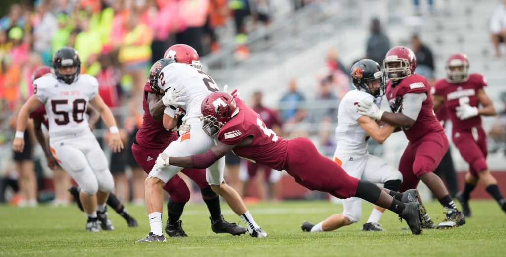 Paul Riley (56) comes in with a diving tackle for a QB sack. Photo/Kevin Sielaff