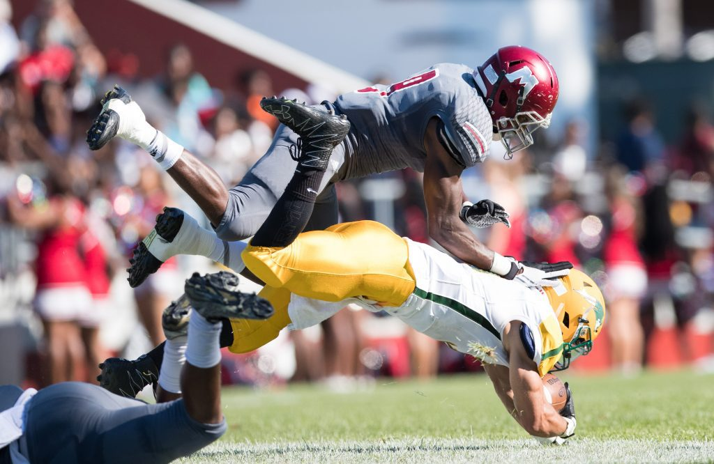 Andrew Ward (9) is tripped up, but he manages to finish a tackle in the air. Photo/Kevin Sielaff