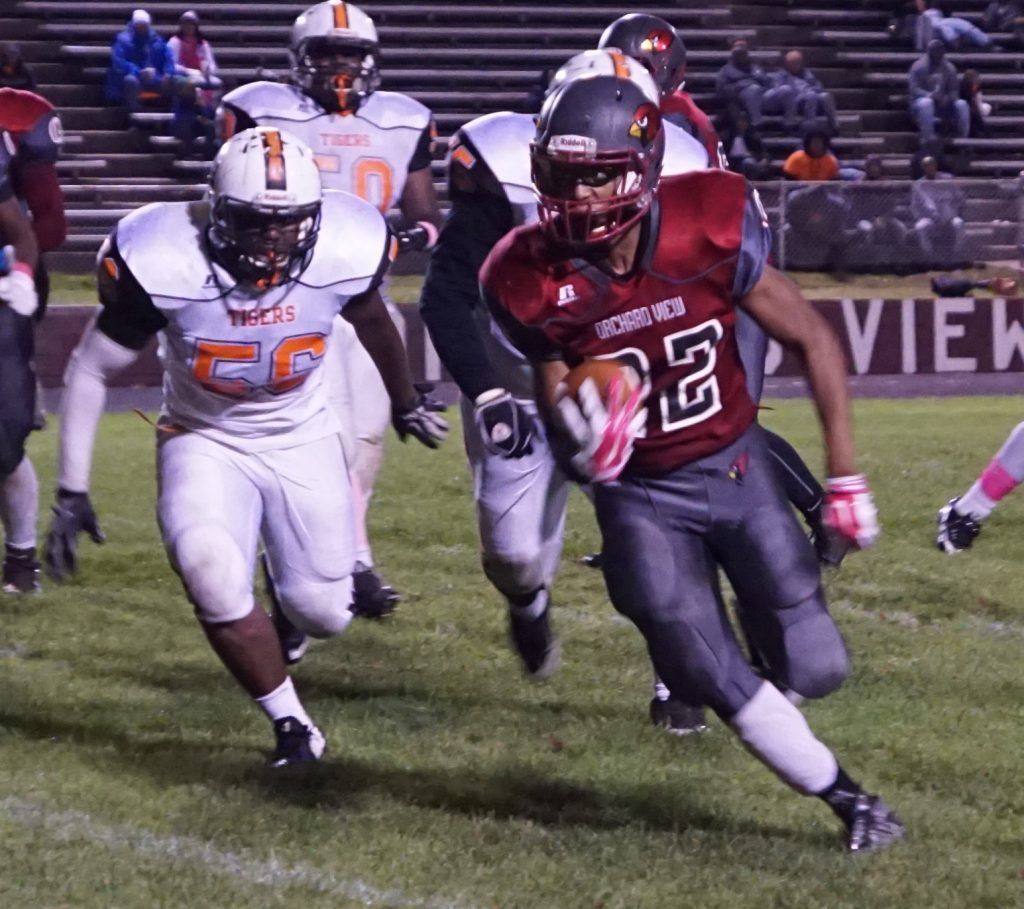 No. 22 Charles Boykins on the OV rush while Muskegon Heights' No. 55 Quinshon Winston pursues. Photo/Leo Valdez