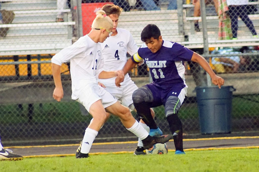 Shelby's No. 11 Carlios Avilez fight's for possession with North Muskegon's No. 11 Dylan Hoffman. Photo/Leo Valdez