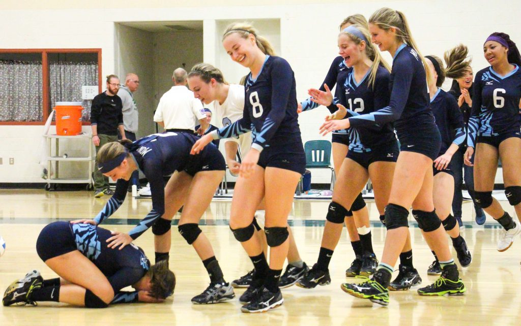 The Mona Shores volleyball team reacts after winning the city title.