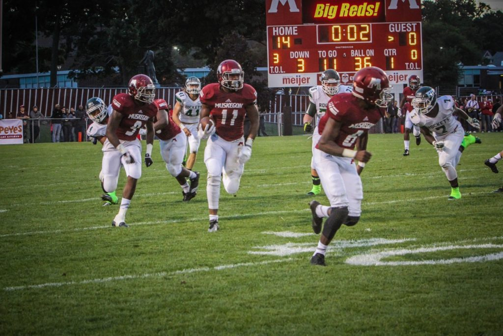 Muskegon's Jacorey Sullivan (11) brings the ball up field with No. 6 Clinton Jefferson Jr. leading and No. 3 Kalil Pimpleton trailing. Photo/Joe Lane