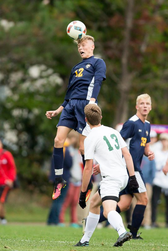 Grand Haven's Ethan King goes up for the header. Photo/Randy Riksen