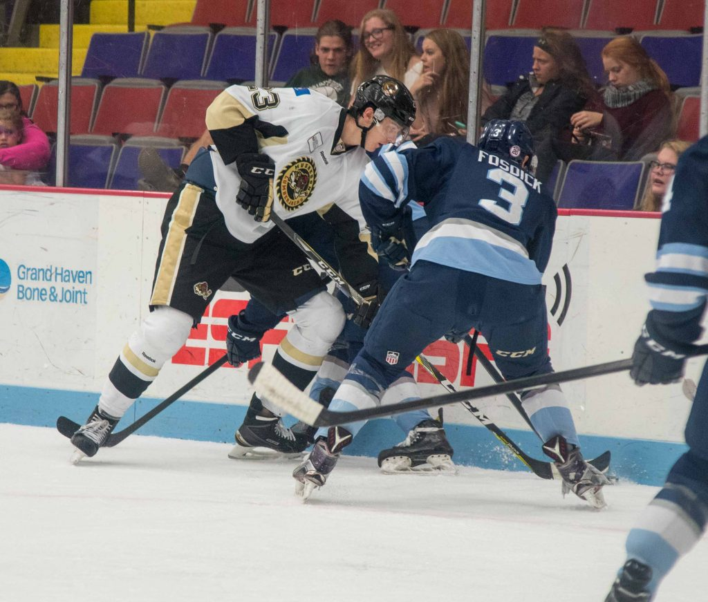 Keenan Suthers battles for the puck along the boards.  (photo/Eric Sturr)