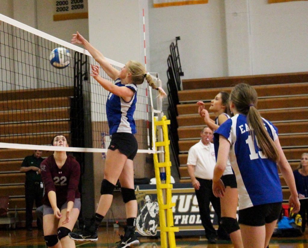 Madison Heiss makes the block to win the match for Fruitport Calvary Christian. Photo/Jason Goorman