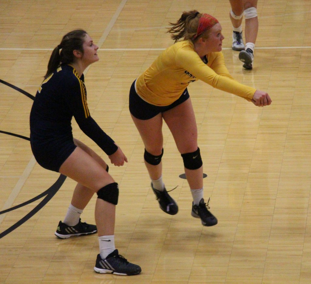 Sophia Newhouse (gold) gets the dig for Grand Haven. Photo/Dave Hart