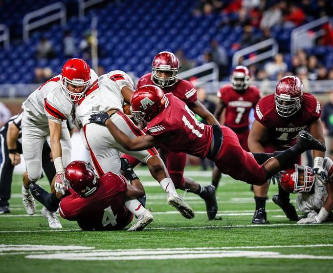 Muskegon defender No. 18 AliVonta Wallace and No. 4 Raquis McDonald take down OLSM runningback No. 22 RaShawn Allen. Photo/Tim Reilly